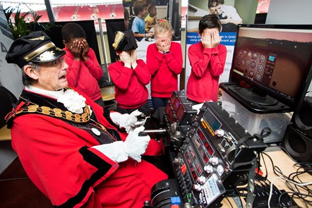 Islington Mayor, Cllr Dave Poyser crashing the flight simulator with children from Tufnell Park Primary School covering their eyes