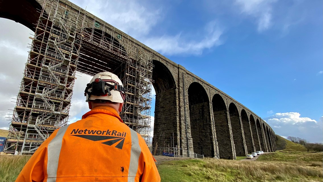 Iconic Ribblehead viaduct repaired for 'Staycation Summer': Ribblehead viaduct with Network Rail worker in the foreground