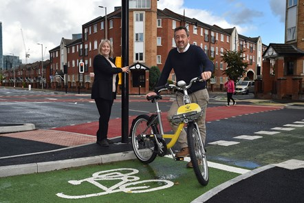 CYCLOPS launch Hulme-5: Close shot of Manchester City Council's Executive Member for Environment, Councillor Tracey Rawlins and Greater Manchester Transport Commissioner, Chris Boardman, using the new CYCLOPS junction in Hulme. Chris Boardman is holding a branded Bee bike.