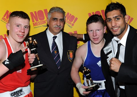 Morgan Jackson (red) from Gloves and John James (blue) from St Josephs in Newport collect their trophies from champion boxer Amir Khan at the No Messin' tri-national boxing competition. Joined by Yaqoob Hussein, from the British Amatuer Boxing Association