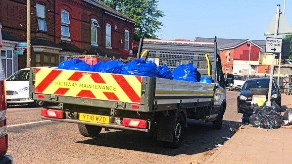 Truck filled with rubbish bags