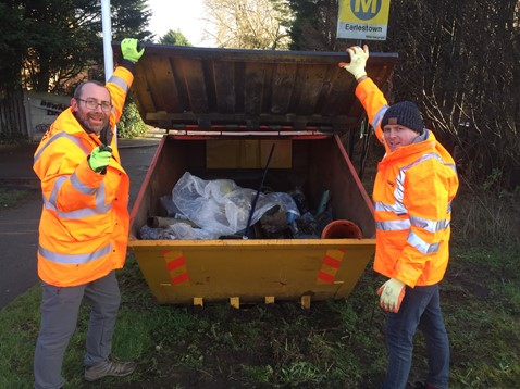 Mark Bellew and Wayne O'Reilly by a skip full of litter at Earlestown station