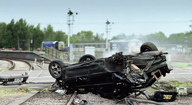 TOUGH SENTENCES NEEDED AS LEVEL CROSSING LAW BREAKING REACHES FIVE YEAR HIGH (ANGLIA): Image of upturned car from tv advert