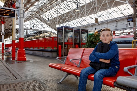 Railway Children Sleepout: Vulnerable young boy (model) sat alone in station