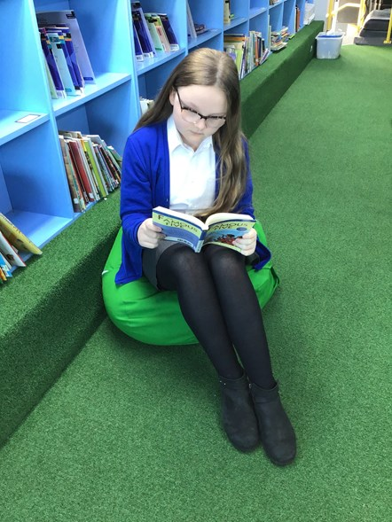 Lily Porter Greswell primary school: Greswell Primary School pupil Lily Porter enjoying reading a book in the school's reading space. The space was created from a decommissioned yellow school bus, donated by TfGM in 2018.