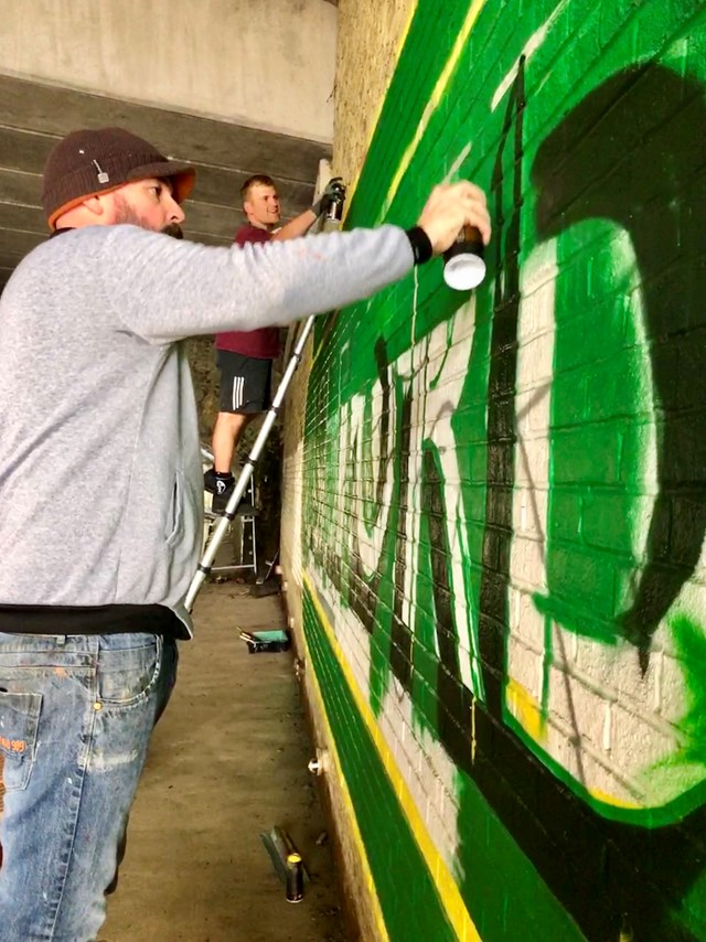 Lionel Stanhope and his team painting mural on wall of passageway in Ashford