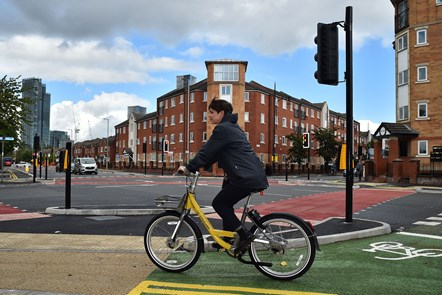 CYCLOPS launch Hulme-6: A side on view of a cyclist using a branded Bee Bike on the new CYCLOPS junction in Hulme.