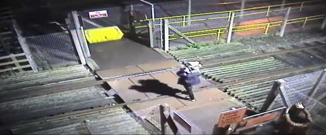 Man runs across level crossing with toddler