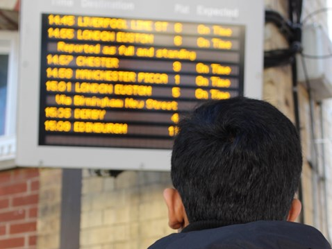 Railway Children Sleepout: Child (model) looking at departure board in station