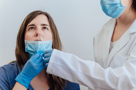 Example of lady receiving swab test from figure dressed in PPE