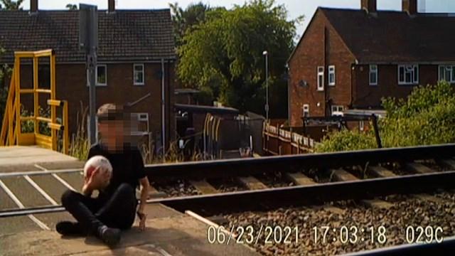 Boy sitting on Jamaica Road level crossing tracks in Malvern