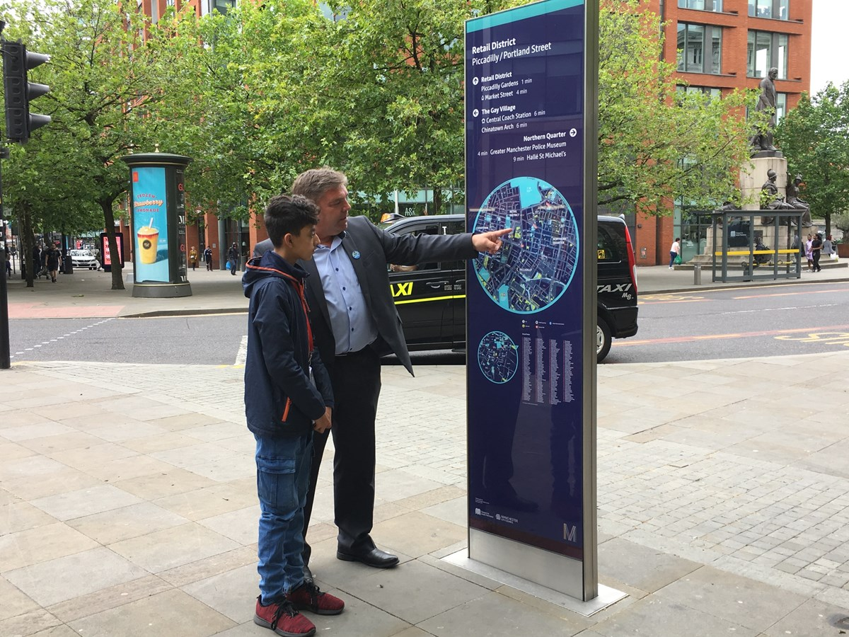 Walking sign on Piccadilly/Portland Street: Councillor Mark Atherton with teenage boy in front of a Walking sign on Piccadilly/Portland Street