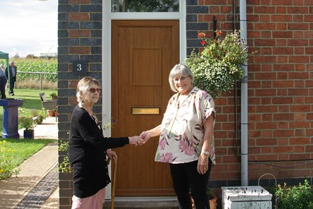 Alison Evans, 4th generation descendant of William Philip Price (left), handing over the keys to Diana Thomas, the new resident of no. 3 (right)