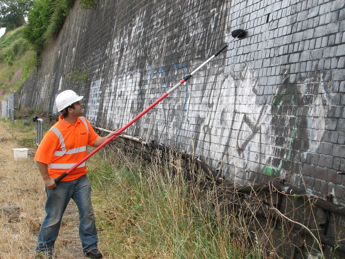 Graffiti clear up - Bristol Temple Meads: Maintenance undertake painting out of graffiti on wall as part of the one mile clean up either side of Bristol Temple Meads station - 31 July 2006