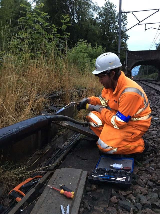 Orange army member repairs damage caused by copper thieves on West Coast main line in Staffordshire