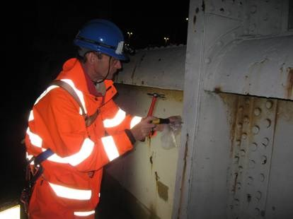 Expert taking samples from bridge to analyse paint system