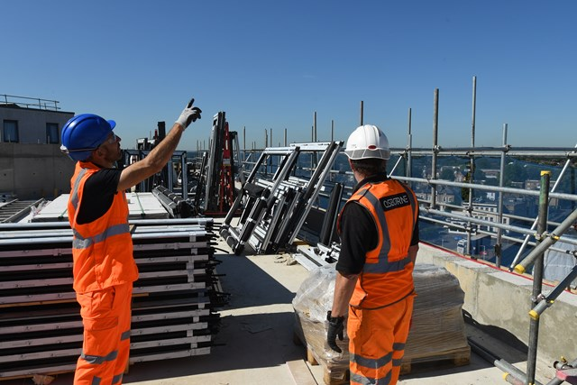 Network Rail to reduce its third party works fees: Engineers on rooftop worksite next to railway