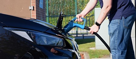 Owner plugging electric car into charging point