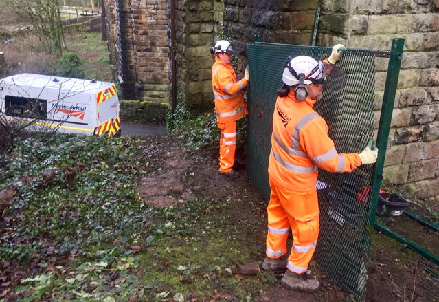 Urgent work to stop trespassers in Uppermill from risking their lives: Network Rail workers installing further railway safety fencing at Den Lane in Uppermill 17 December 2018