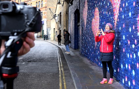 A passer by poses with Jimmy C's art in Southwark