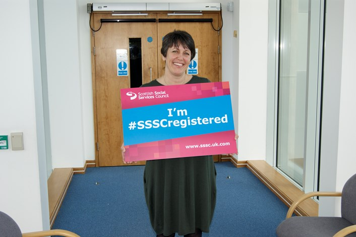 Woman holding a sign saying she is SSSC registered