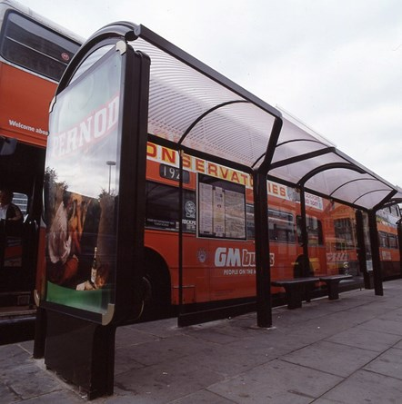 Bus shelter with 192 GM buses double decker bus on Piccadilly, Manchester: A bus shelter in front of a 192 GM buses double decker bus on Piccadilly, Manchester. Shelter features a Pernod advert.