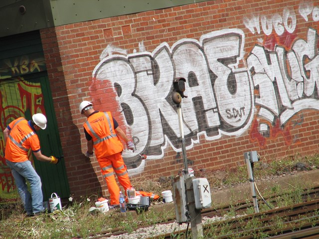 Tackling graffiti - Bristol Temple Meads: Maintenance team tackle huge amount of graffiti on line side building as part of the one mile clean up either side of Bristol Temple Meads station, 31 July 2006