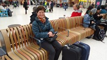 Satisfied rail passenger sitting on new seating at Victoria station