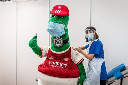 Arsenal mascot Gunnersaurus (left) gets a Covid-19 jab from a frontline member of staff at an Islington vaccination centre: Arsenal mascot Gunnersaurus (left) gets a Covid-19 jab from a frontline member of staff at an Islington vaccination centre