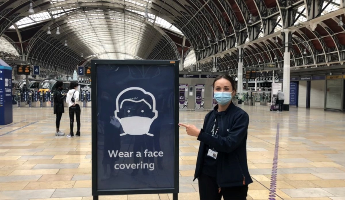 Network Rail employee with face coverings sign at Paddington station: Credit: Network Rail