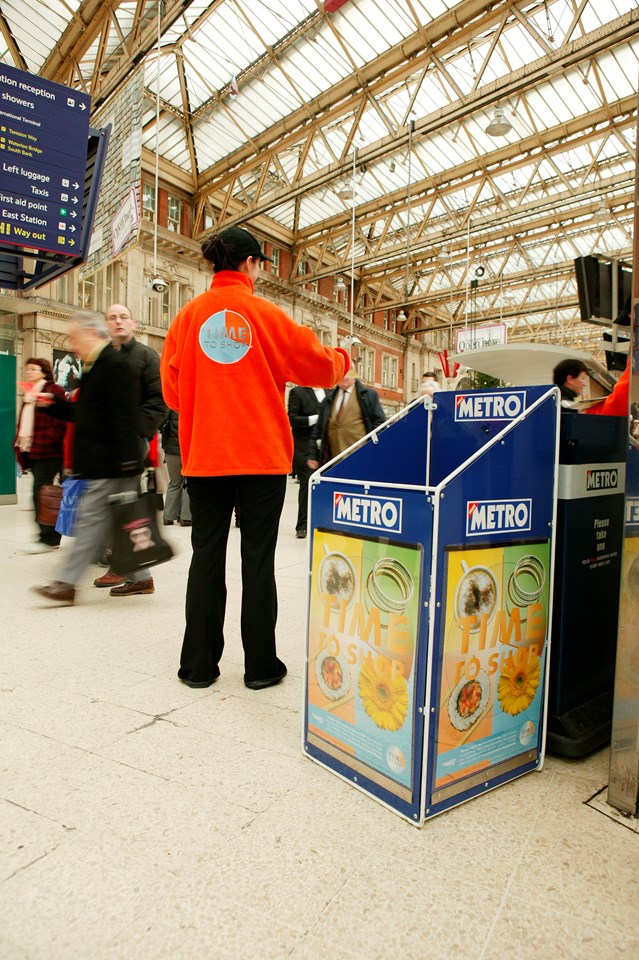 Time to Shop 3: One of Network Rail's 'Time to Shop' team gives discount leaflets to busy Christmas shoppers at Waterloo station