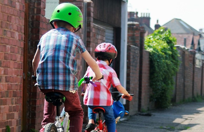 Young boys riding bikes to school: School Streets providing safer travel to school