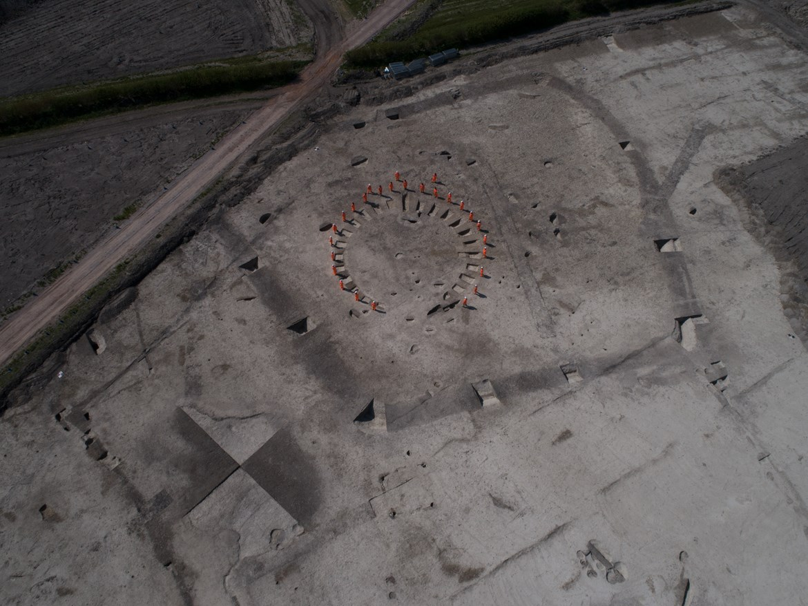 Wellwick Farm Archaeology Aerial Jul 2020: Credit: Infra Archaeology  Archaeologists stood on the outline of a horse-shoe shaped funerary enclosure, likely Iron Age in date. At Wellwick Farm, archaeologists believe the Bronze Age and Iron Age saw the addition of some domestic occupation with at least one roundhouse identified and possible structures such as animal pens and pits used for disposing food.   Internal Asset No. 16776