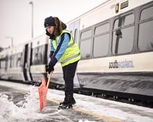 Platform staff shovelling snow at Dartford