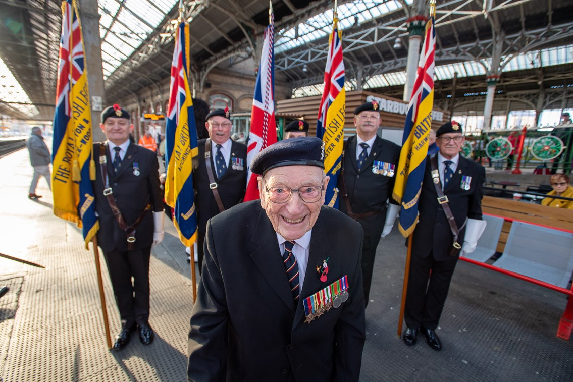 Ernest Horsfall smiling in front of standard bearers from the Royal British Legion's Preston branch