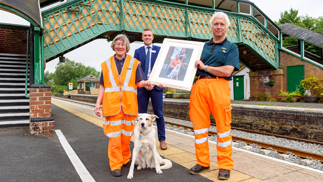 Tom and Sue Baxter with beloved dog Rosie and Christian Irwin of Network Rail: Tom and Sue Baxter of the Dartmoor Railway Association were presented with a framed photo by Christian Irwin, Network Rail industry programme director.
