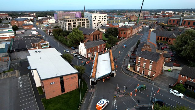 Drone shot of new bridge being slowly driven to Warrington Central station