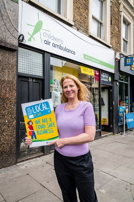 Joanna Phillips, manager of the Children's Air Ambulance charity shop in Junction Road, Archway, promoting the Covid-Safe Business Award scheme window stickers