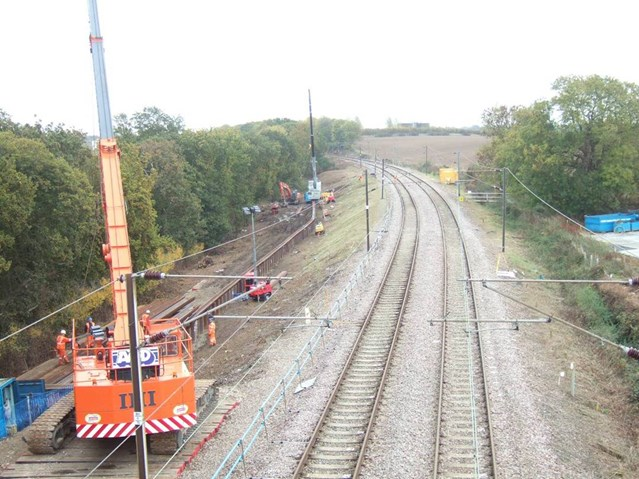 WRABNESS LANDSLIP: HARWICH BRANCH LINE REOPENS SIX DAYS EARLY AFTER HEROIC EFFORTS: Copperas Wood embankment - new piling