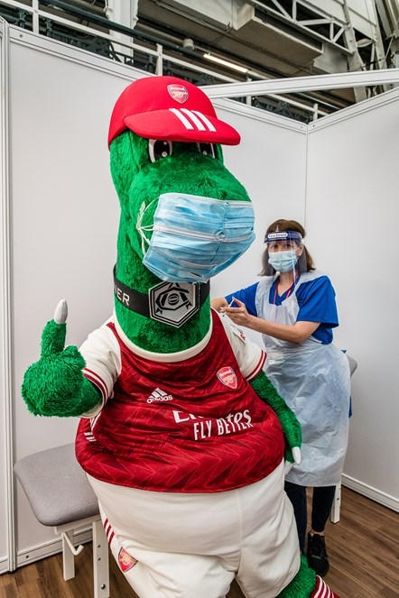 Arsenal mascot Gunnersaurus (left) gets a Covid-19 jab from a frontline member of staff at an Islington vaccination centre