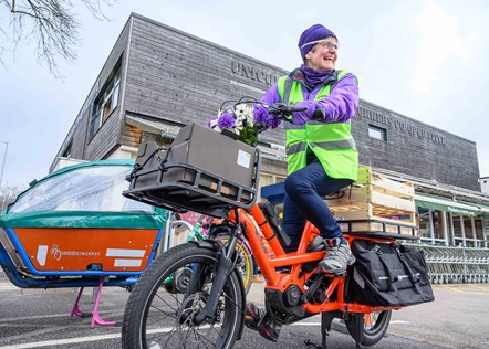 TfGM Gylnis on cargo bike in front of grocery store