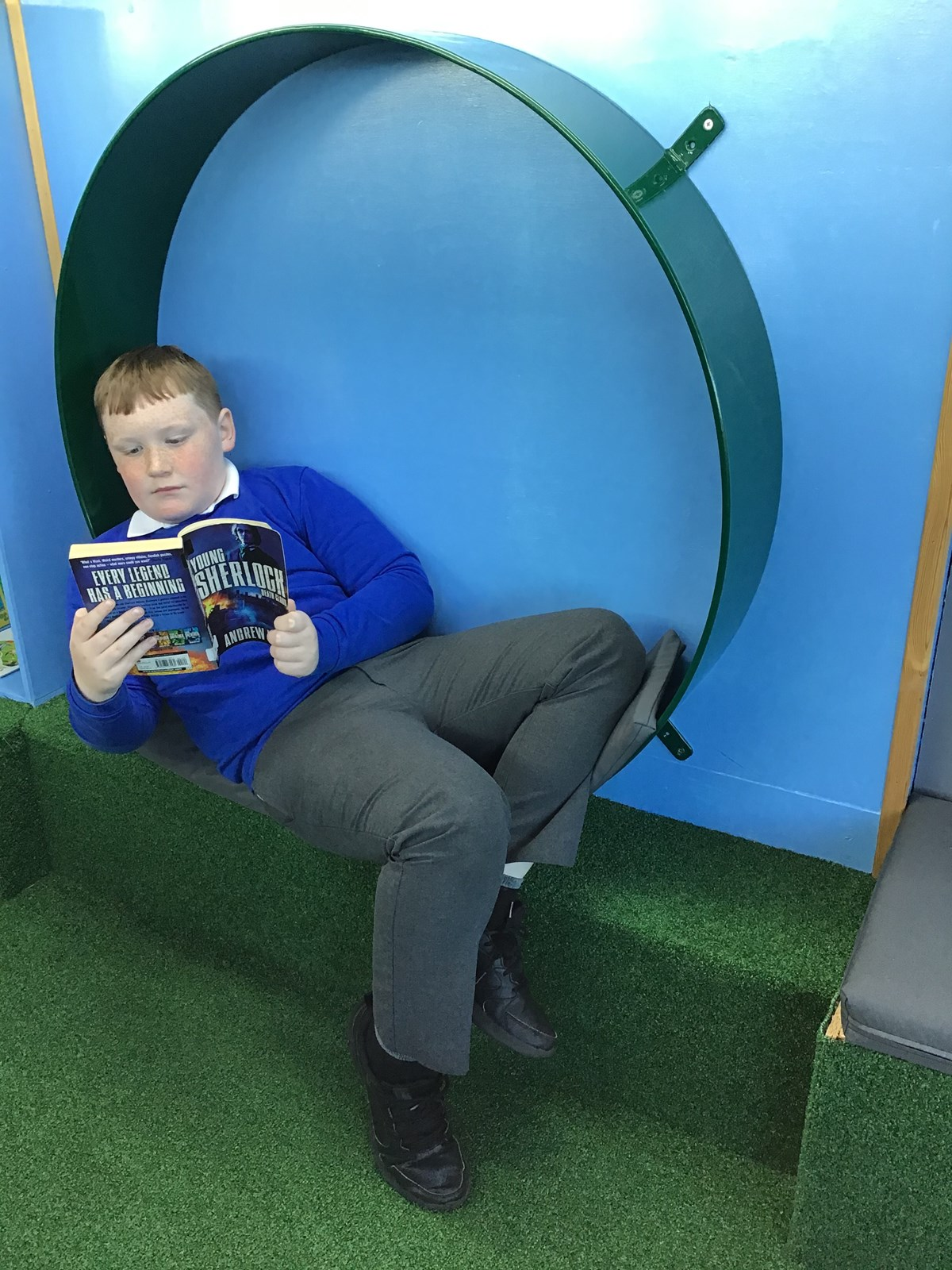 Dylan Wood Greswell Primary School: Greswell Primary School pupil Dylan Wood enjoying reading a book in the school's reading space. The space was created from a decommissioned yellow school bus, donated by TfGM in 2018.