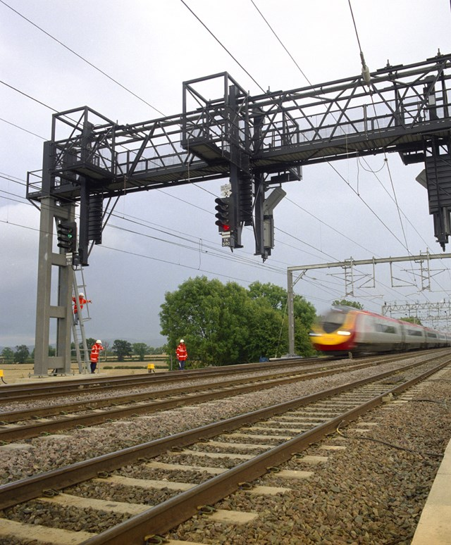 New signal gantry: New signal gantry on the West Coast Main Line with Pendolino passing and men working