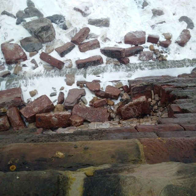 Network Rail assessing track and sea wall damage on the Cumbrian coast line: Sea wall breach at Parton