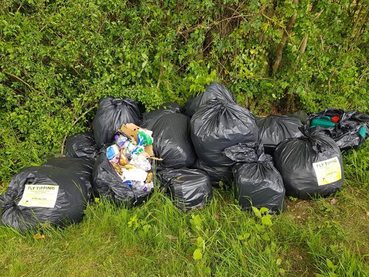 A pile of refuse sacks against a hedge with fly tipping notices attached