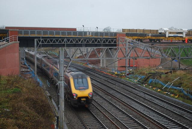 Stafford railway upgrade scheme sets track-laying record: NTC (track-laying) train passes over existing WCML at Norton Bridge on new flyover (XC Voyager beneath)